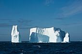 Ein Eisberg, einst viel größer, aber jetzt mit drei Türmen, schwimmt im offenen Meer, in der Nähe von South Shetland Islands, Antarktis