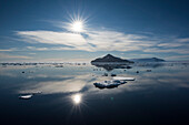 A bright sun shines on a seascape with calm waters, sea-ice and a distant island, Paulet Island, Antarctic Peninsula, Antarctica