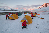 Passengers of an expedition cruise ship MS Bremen (Hapag-Lloyd Cruises) set up their overnight camp on a flat stretch of well-packed snow, near Port Lockroy, Wiencke Island, Antarctica