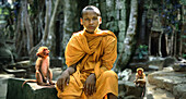 Monk and monkeys outside a temple in Angkor, Angkor, Siem Raep, Cambodia, Asia