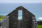 The waves of the Atlantic Ocean seen through the window of the remnants of an old stone building without a roof seen from while walking the Dingle Way, Dingle Peninsula, County Kerry, Ireland, Europe