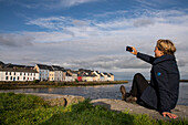 A blond woman in a blue jacket and hiking boots takes a selfie photo with the Long Walk with its row of beautiful coloured houses situated at the Corrib Harbour behind, Galway, County Galway, Ireland, Europe