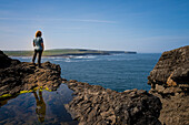At the lookout point near Georges Head on the Cliffs of Kilkee, a woman stands on rocks and looks out over the coastline, Byrnes Cove, Kilkee, County Clare, Ireland, Europe