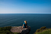A blonde woman sits on a rock and overlooks the blue sea on the horizon, seen from while walking the Dingle Way, Ballydavid North, Brandon, Dingle Peninsula, County Kerry, Ireland, Europe