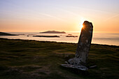 Sunset on the set of Star Wars: Slea Head with a menhir in the foreground and the sleeping giant in the background seen from while walking the Dingle Way, Slea Head, Dingle Peninsula, County Kerry, Ireland, Europe