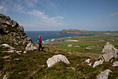 Hiker on rocky trail with green fields overlooking the sunny coast seen from while walking the Dingle Way, Dingle Peninsula, County Kerry, Ireland, Europe