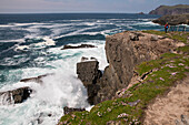 A woman stands along rocks and overlooks the Atlantic Ocean as spray from waves rages, seen from while walking the Dingle Way, Dingle Peninsula, County Kerry, Ireland, Europe