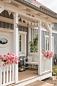 Front porch of custom home with white bench and flowerspots in sunlight, Korbach, Hesse, Germany, Europe