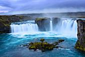 Die türkis-weiß leuchtende Gischt des Wasserfalls Godafoss, Island, Europa
