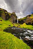 Blick auf die Felsenlandschaft am Wasserfall Kvernufoss, im Vordergrund der Fluss, Island, Europa