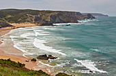Steep coast and surfers at Praia de Amado beach near Carrapateira, Parque Natural do Sudoeste Alentejano e Costa Vicentina, Atlantic Ocean, District Faro, Region of Algarve, Portugal, Europe