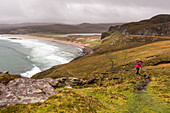 A hiker on the hillside of Sandwood Bay, Highlands, Scotland, United Kingdom