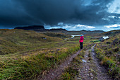 A hiker at Suileag Bothy, clouds in front of the Suilven, Inverpolly Nature Reserve, Highlands, Scotland, UK