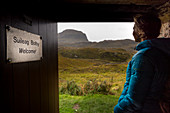 A female walker looks out from the Suileag Bothy, Inverpolly Nature Reserve, Highlands, Scotland, UK