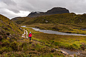 A walker on the way to Suilven, Inverpolly Nature Reserve, Highlands, Scotland, UK