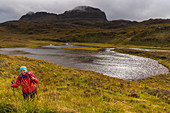A female walker at a body of water below the Suilven, Inverpolly Nature Reserve, Highlands, Scotland, UK