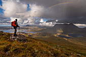 Hiker looks out from Stac Pollaidh on Loch Sionasgaig and Cul Mor, Inverpolly Nature Reserve, Highlands, Scotland, UK