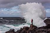 Eine Frau steht vor der Brandung des Meeres bei Sheigra, Wellen brechen am Felsen, Highlands, Schottland, Großbritannien