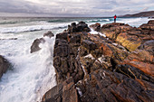 A man stands on a rock in front of the surf at Sandwood Bay, Highlands, Scotland, UK