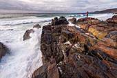 Ein Mann steht auf einem Felsen vor der Brandung an der Sandwood Bay, Highlands, Schottland, Großbritannien