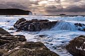 Gischt spritzt über Felsen an der Sandwood Bay, Highlands, Schottland, Großbritannien