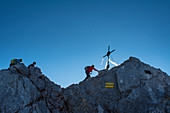 Climbers on arrival on the center peak of Watzmann, summit cross in front of blue sky, Berchtesgaden Alps, Berchtesgaden, Germany