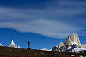 A hiker spreads his arms with trekking sticks, Fitz Roy & Cerro Torre in the background, Los Glaciares National Park, Patagonia, Argentina