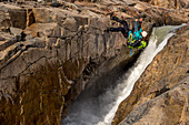 A female hiker crosses the Rio Electrico on a zip line (Tirolesa), Los Glaciares National Park, Patagonia, Argentina