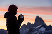 A female walker drinks coffee in front of the morning silhouette of Fitz Roy, Los Glaciares National Park, Patagonia, Argentina