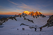 Climbers during the ascent to the Aiguille Rochefort, sunrise at Mont Blanc in the background, Mont Blanc group, Chamonix, France