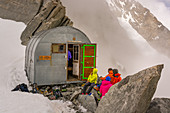 Climbers in front of the bivouac Ettore Canzio, Grandes Jorasses, Mont Blanc group, France