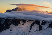 The Aiguille Verte and glaciers at sunrise, clouds in the foreground, Mont Blanc group, France