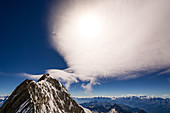 Summit of the Grandes Jorasses with the sun obscuring clouds, Mont Blanc group, France