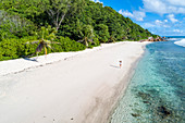 A woman strolling along Anse Fourmis beach. La Digue, Seychelles, Africa