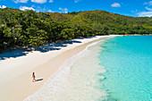 Eine Frau läuft am Strand Anse Lazio, Praslin Insel, Seychellen, Afrika