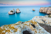 The Two Sisters stacks in front of the shore of Torre dell'Orso. Melendugno, province of Lecce, Salento, Apulia, Italy.