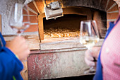 a detail of two glasses of wine with a bread oven in the background, bolzano province;italy;south tyrol;trentino alto adige