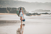 A woman with a surfboard on the coast of northern Spain walks along the beach