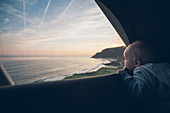Toddler looks out of a tent on the coast of northern Spain