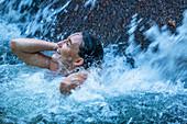 Eine Frau erfrischt sich unter einem Wasserfall in Phuket, Thailand