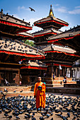 Nepalese Monk wearing orange robe holding urn for alms at Durbar Square Kathmandu, Nepal, Nepalese, Asia, Asian, Himalayan Country, Himalayas.