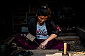 Young woman carving wood in Bhaktapur alleys, Nepal, Nepalese, Asia, Asian, Himalayan Country, Himalayas.