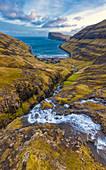 Aerial panoramic of torrent flowing toward sea, Tjornuvik, Streymoy island, Faroe Islands, Denmark