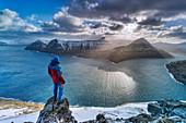 Hiker on rocks admiring the rays of sun over Funningur fjord, Eysturoy island, Faroe Islands, Denmark