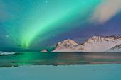 Aurora Borealis over Haukland beach covered with snow, Vestvagoy, Nordland, Lofoten Islands, Norway