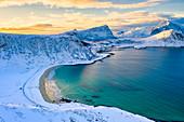 Aerial view of Haukland beach surrounded by snowy peaks, Vestvagoy, Nordland, Lofoten Islands, Norway