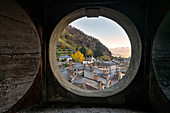 Old buildings of traditional Seriole neighborhood seen through an opening slit inside Palazzo Malacrida, Morbegno, province of Sondrio, Valtellina, Lombardy, Italy