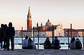 People sitting on the bank in front of San Giorgio Maggiore island, Venice, Veneto, Italy, Europe