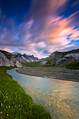 Clouds are reflected in the stream during a windy sunrise. Unterer Segnesboden, Flims, District of Imboden, Canton of Grisons, Switzerland, Europe