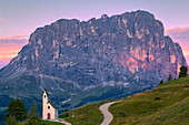 San Maurizio Chapel at sunrise with Sassolungo in the background. Gardena Pass, Gardena Valley, Dolomites, South Tyrol, Italy, Europe, Europe.